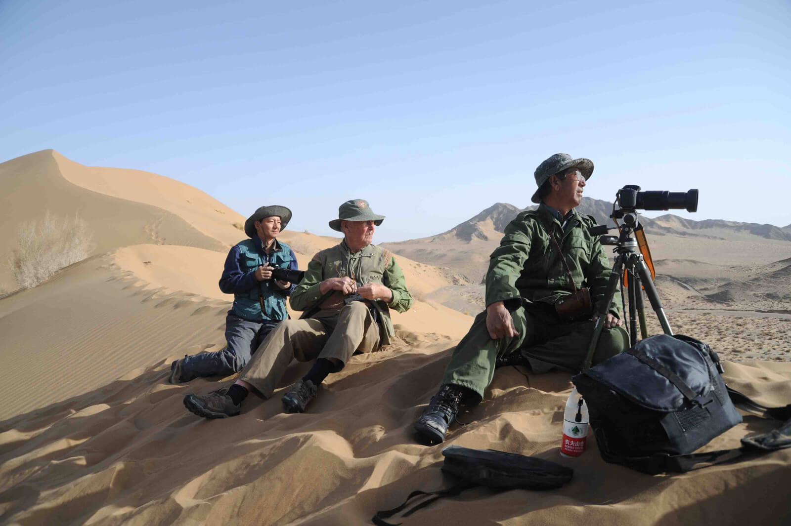 John Hare and Chinese scientists above Kum Su spring looking for wildlife. 2006, Desert of Lop, China